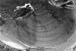 Photographie aérienne de l'arrivée de la houle dans une baie